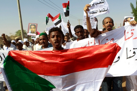 A man holds a Sudanese flag as he chants slogans during a demonstration after Friday prayers in north Khartoum