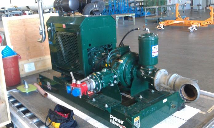 Pumpeneinlass und -auslass - Dieses Bild zeigt den Dieselmotor, der das System antreibt.  Die Pumpe selbst ist das große scheibenförmige Element links vom großen Zylinder, aus dem ein Schlauch herausragt.