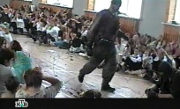 This TV grab image taken from Russian NTV channel 07 September 2004 shows a gunman walking as hostages sit in the gymnasium of the Beslan school, northern Ossetia. Russia's NTV television aired a tape 07 September it said was made by the hostage takers showing what seemed to be the first hours of the three day school crisis that ended in the deaths of more than 335 people and 31 hostage takers. AFP PHOTO / NTV