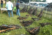 A man inspects firearms surrendered by pro-government militia in Shariff Aguak, Maguindanao province, southern Philippines, Thursday, Nov. 26, 2009. A scion of a powerful clan suspected in the massacre of 57 people in an election caravan in the southern Philippines turned himself in Wednesday amid mounting pressure on the government to crack down on lawlessness and warlords. (AP Photo/Froilan Gallardo)