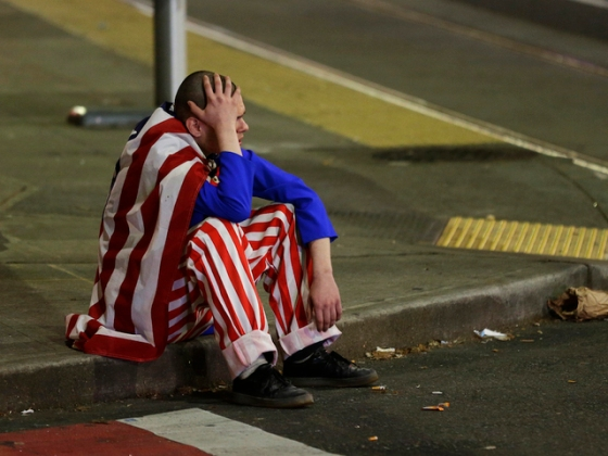 A man dressed in red-white-and-blue sits on the curb during a protest against President-elect Donald Trump, Wednesday, Nov. 9, 2016, in Seattle's Capitol Hill neighborhood. (AP Photo/Ted S. Warren)