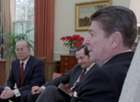 """Walter Raymond Jr., a CIA propaganda and disinformation specialist who oversaw President Reagan's """"perception management"""" and psyops projects at the National Security Council. Raymond is partially obscured by President Reagan and is sitting next to National Security Adviser John Poindexter.. (Photo credit: Reagan presidential library)"""
