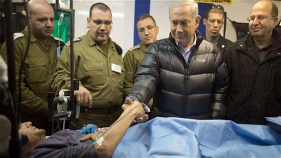 The file photo shows Israeli Prime Minister Benjamin Netanyahu shaking hands with a militant in an Israeli field hospital in Syria's occupied Golan Heights.