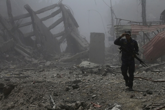 An Iraqi soldier walks through the ruins of Mosul (Reuters)
